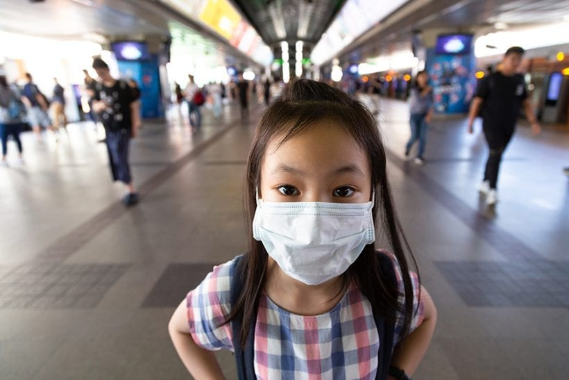 Asian girl is wearing white protective mask in the crowd of people,health concept