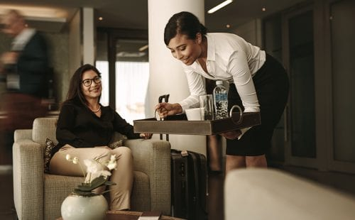 Airport lounge waitress serving coffee to female passenger||||ZURICH