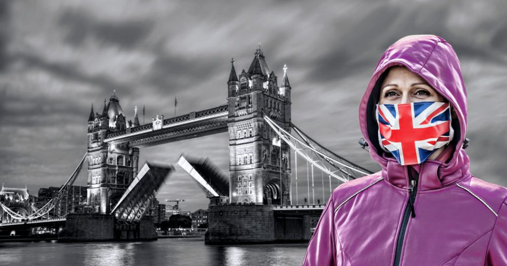 Woman wearing protection face mask with British flag against coronavirus in front of the Tower Bridge, London, England